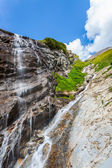 Mountain stream forming a small waterfall — Stock Photo