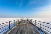 Wooden pier on the frozen sea — Stock Photo