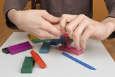 Boy moulds from plasticine on table — Stock Photo