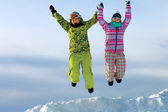 Snowboarders friends in bright vivid clothes jumping — Stock Photo