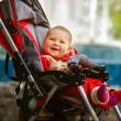 Smiling baby in sitting stroller on nature — Stock Photo