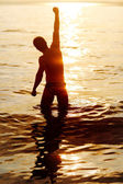 Man with his hand up on the dawn on the beach — Стоковое фото
