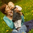 Young mother with her little baby on the meadow — Stock Photo #45656571