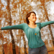 Young woman arms raised enjoying the fresh air in autumn forest — Stock Photo #47594451