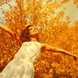 Young woman arms raised enjoying the fresh air in autumn forest — Stock Photo #47769161