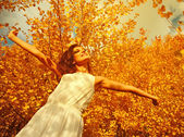 Young woman arms raised enjoying the fresh air in autumn forest — Stock Photo