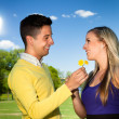 Portrait of a young couple smiling outside with flowers — Stock Photo