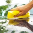 Hand car wash with yellow sponge - Stock Photo
