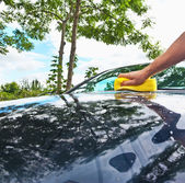Hand car wash with yellow sponge — Stock Photo