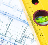 Spirit level and architectural drawings — Stock Photo