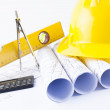 Yellow helmet and heap of project drawings and construction tools — Stock Photo #38354181