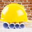 Yellow helmet and heap of project drawings and construction tools — Stock Photo #38355613