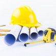 Yellow helmet and heap of project drawings and construction tools — Stock Photo #38358773