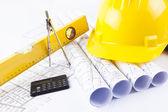 Sarı kask ve proje çizim ve inşaat araçları yığın — Stok fotoğraf