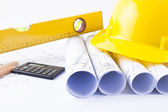 Yellow helmet and heap of project drawings and construction tools — Stock Photo