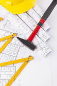 Red hammer and construction tool with architectural drawing — Stock Photo