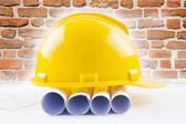 Yellow helmet with level and project drawings — Stock Photo