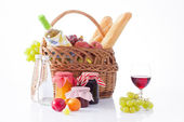 Picnic basket with bottle of wine,fruits, bread and summer hat isolated on white — Stock Photo