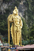 BATU CAVE, MALAYSIA - JAN 17 : Photo of lord murugan statue standing tall in front the cave entrance taken during Thaipusam on January 17, 2014 at Batu Cave temple, Malaysia . — Stock Photo