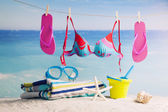 Bright beach accessories, on blue sea background — Stock Photo