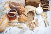 Rustic bread and wheat on an old vintage planked wood table. background with free text space — Stock Photo