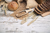 Rustic bread and wheat on an old vintage planked wood table. background with free text space — Stockfoto