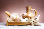 Freshly baked french bread with homespun fabric and wheat spikes on white background. — Stock Photo