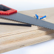 Hacksaw on plywood boards with colored dowels — Stock Photo