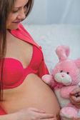 グッズを保持している赤い下着で妊娠中の女性 — ストック写真