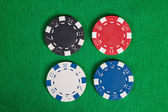 Four macro poker chips on green table — Stock Photo