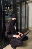 Robber in black mask hack server room downloading data on laptop — Stock Photo