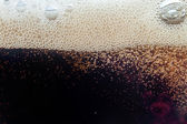Macro bubble and  foam on the glass wall of cola — Stock Photo