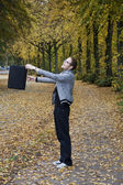 Man swinging bag in the park — Stock Photo