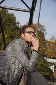 Young man smokes on a bridge — Stock Photo