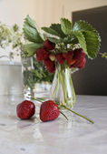 strawberries and flowers on the table — Stock fotografie