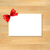 Red Bow And Blank Gift Tag With Wooden Wallpaper — Stockvector