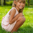 Little girl sits on the grass in the park - Stock Photo