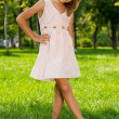 Smiling little girl stands in the park - Stock Photo