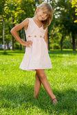 Lächelnd mädchen steht im park — Stockfoto