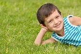 Fröhliche kleine junge auf dem rasen — Stockfoto