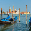 Gondolas at the pier in Venice - Stock Photo