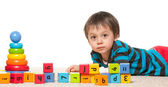Little boy near blocks with alphabet — Stock Photo