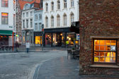 Woman walks by old street of Bruges — Stock Photo