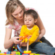 Stock Photo: Mother and son on floor with toys