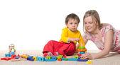 Moeder en zoon op het tapijt met speelgoed — Stockfoto