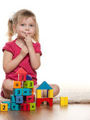 Pensive little girl near toys — Stock Photo