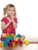 Pensive little girl near toys — Stock Photo