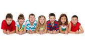 Seven children lying on floor — Stock Photo