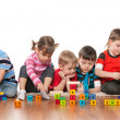 Stock Photo: Five kids playing on floor