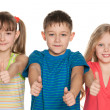 Three children hold their thumbs up - Stock Photo